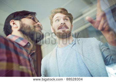 Young businessmen discussing announcements on board in office