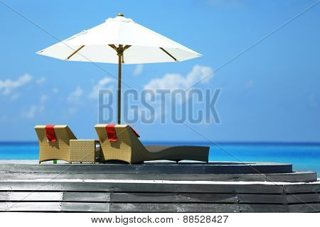 View of place for rest with sunbed and parasol in Baros Maldives