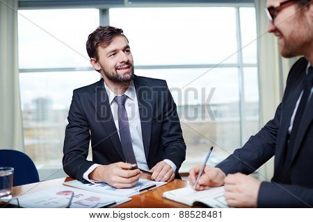 Young businessman listening to his colleague at meeting