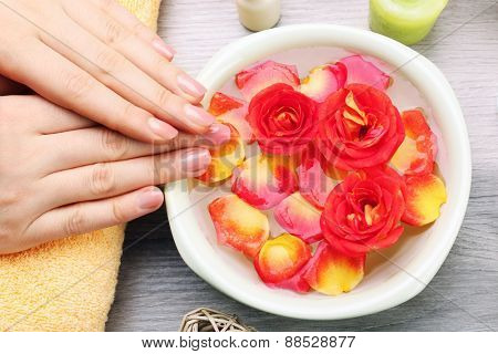 Female hands with bowl of aroma spa water on wooden table, closeup
