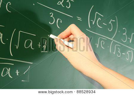 Teacher hand writing formulas on blackboard background