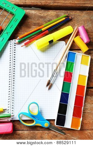 Notebook and bright school stationery on old wooden table