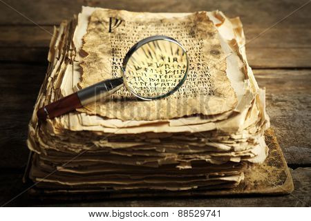 Grunge papers with hieroglyphics with magnifier on wooden background