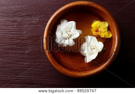 Flower floating in bowl, close-up, on wooden table background