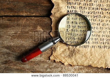 Grunge paper with hieroglyphics with magnifier on wooden background