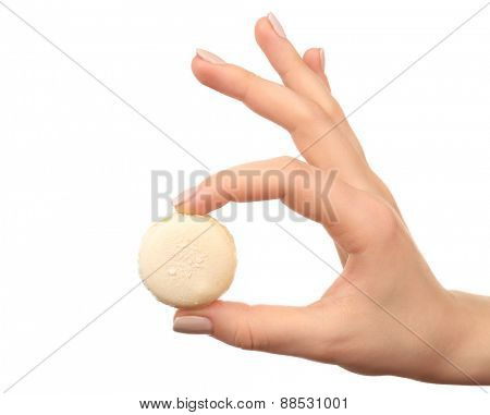 Tasty colorful macaroons in female hand isolated on white