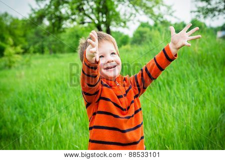 boy on green grass with raised hands
