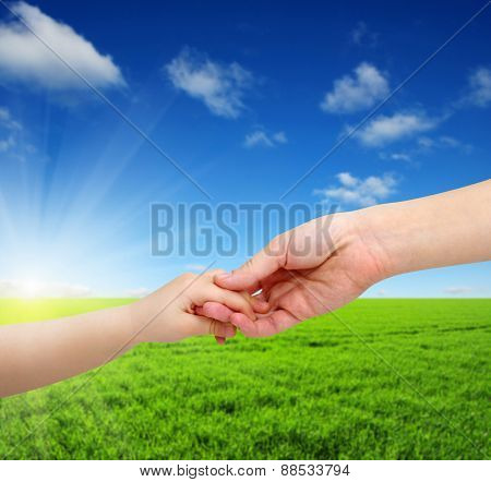 mother gives a hand of a child on landscape