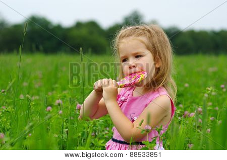 cute little girl eating a lollipop on the field