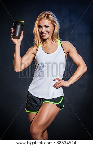 Athletic woman smiling fitness model with protein drink