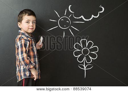 Cute little kid next to a chalkboard