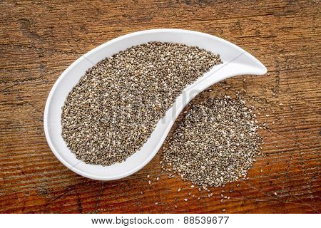 chia seeds in a teardrop shaped bowl - top view against rustic wood