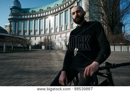 bald bearded guy on black fix against building