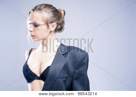 Fashion Concept: One Sexy And Sensual Caucasian Woman Dressed In Gray Suite Posing Against Gray Back