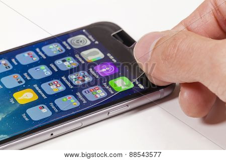 Applying screen protector on mobile phone