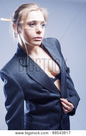 Caucasian Sexy Blond Woman Dressed In Stylish Gray Suite. Wearing Black Lingerie. Against Gray Backg