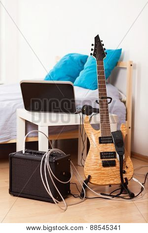 Guitar with an amplifier at home.