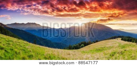 Mountains glow by sunlight. Morning overcast sky. Dramatic scenery. Carpathian, Ukraine, Europe. Beauty world.