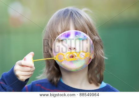 Boy With Blond Hair Blowing Bubbles