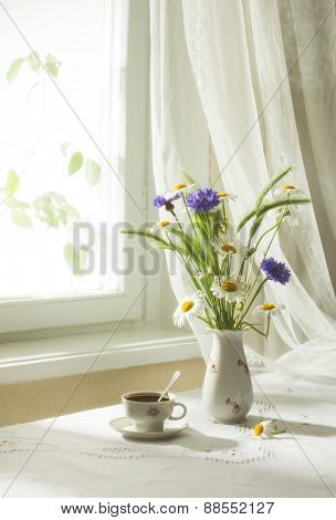 Retro still life with  a bouquet of wildflowers and cup of coffee. Soft focus.