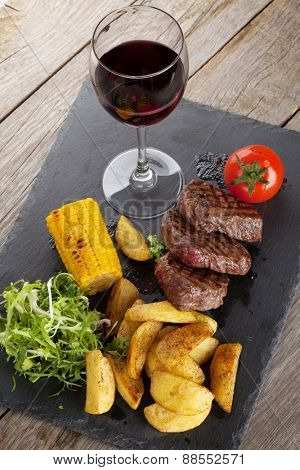 Steak with grilled potato, corn, salad and red wine on wooden table