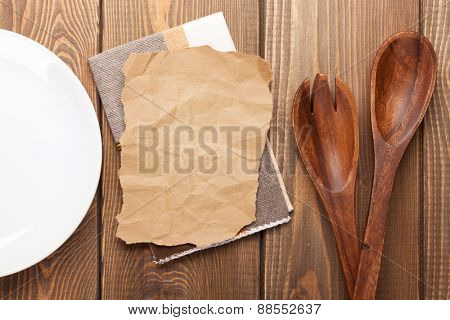 Kitchen utensils over wooden table background with paper for copy space