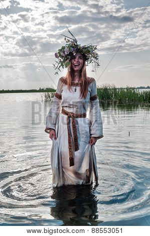 Beautiful woman with flower wreath stands in water