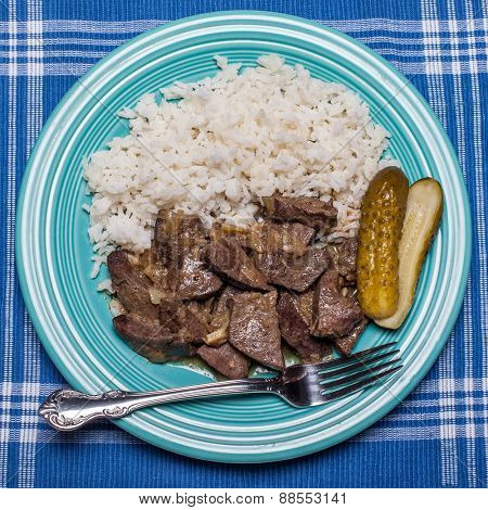 Pork livers with onion pickles and rice on green plate