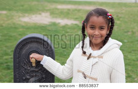 Pretty african little girl in recess by a fountain