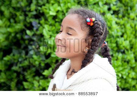 Pretty african girl with winter clothes in the park smelling