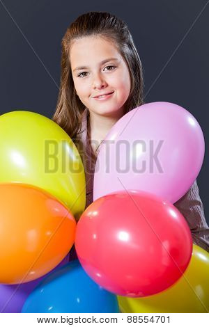 Ten year old caucasian girl with long hair posing in the studio with ballons