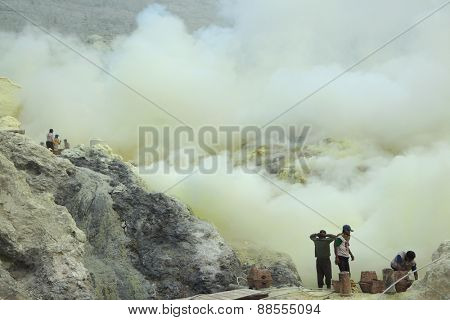 KAWAH IJEN, INDONESIA - AUGUST 10, 2011: Miners collect sulphur in the fumes of toxic volcanic gas at the sulphur mines in the crater of the active volcano of Kawah Ijen, East Java, Indonesia.