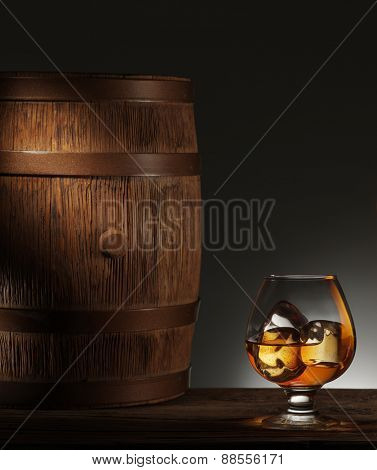 Glass of matured whiskey with ice cubes in it and old wooden barrel.