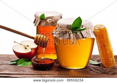 Glass cans full of honey, apples and honeycombs wood. File contains clipping paths.