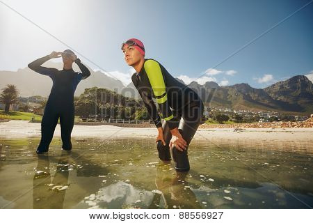 Determined Athletes In Wet Suits Preparing For Triathlon