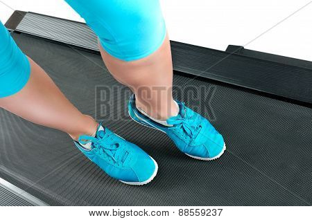 Female Legs In Turquoise Sneakers On A Treadmill.