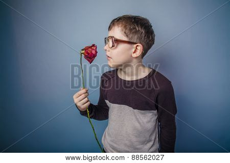 boy teenager European appearance in sunglasses holding and smell