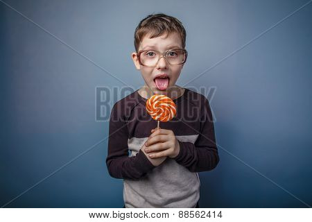 boy teenager European appearance in sunglasses licks candy brigh