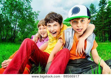 Three joyful children sitting on the grass in the park. Summer.