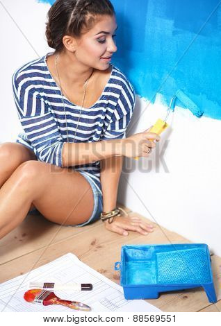 Beautiful young woman doing wall painting, sitting
