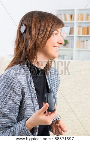 Young, smiling woman showing cochlear implant
