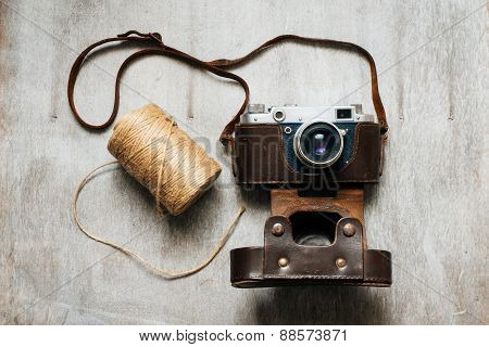 Retro Camera And A Skein Of Thread On Wooden Background