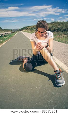 Athletic woman touching knee by painful injury in training