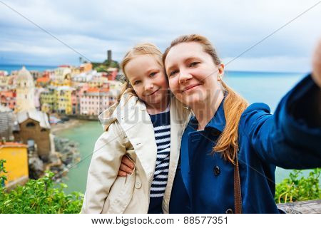 Mother and daughter taking selfie with smartphone having scenic view of colorful village Vernazza, Cinque Terre, Italy on background