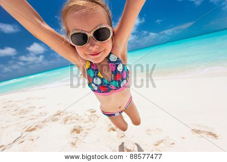 Little girl having fun with her dad at beach