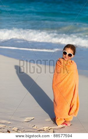 Cute little girl at tropical beach covered with towel