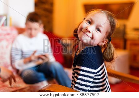 Casual portrait of adorable happy little girl at home