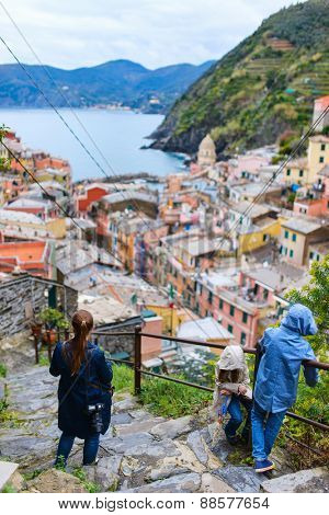 Family of mother and kids enjoying scenic view of colorful village Vernazza, Cinque Terre, Italy