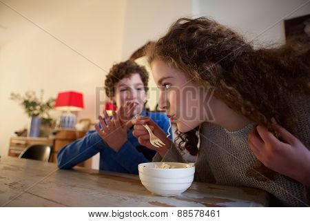 Brother And Sister Sitting At Dining Room Table Eating Food