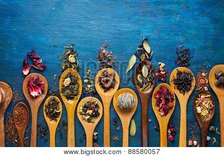 Dry tea with in wooden spoons.